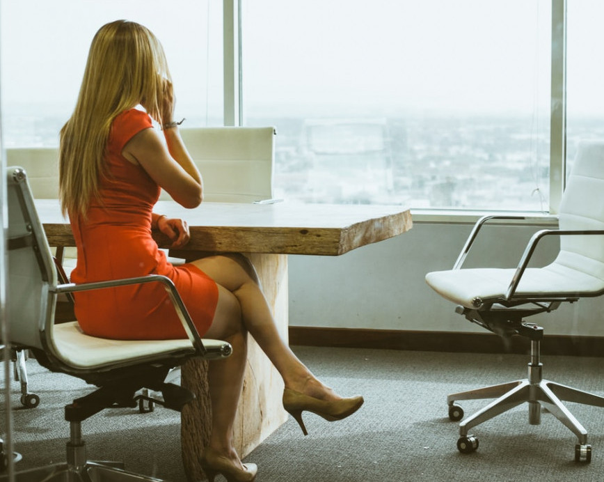 blond woman sitting at a table dressed in a orange dress looking out the window