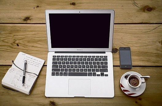 laptop, cup of coffee, and a paperblock on a table