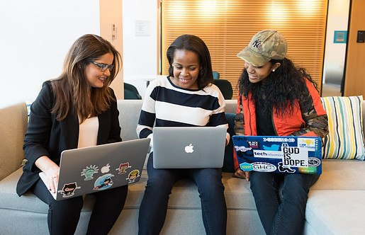 three women with laptops working, smiling, and watching