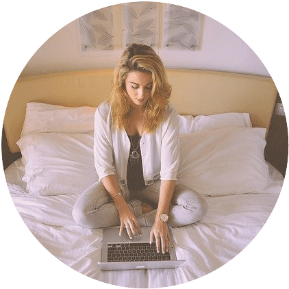 woman sitting on a bed, working on her laptop