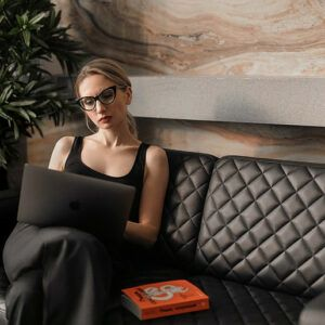 woman dressed in black with a laptop on her knies sitting on a black leather sofa