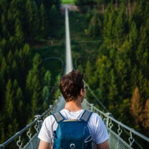 a backpacker is crossing a high hanging bridge
