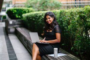 indian woman sitting on a bench working on a laptop