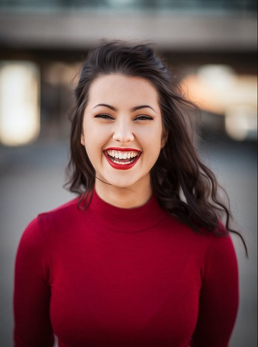 woman with long dark hair in a red colored pullover, laughing