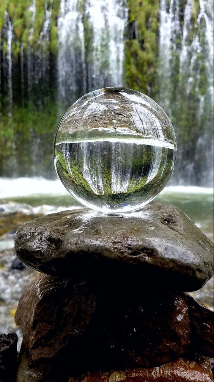 a cristal ball in front of a waterfall, mirroring the waterfall