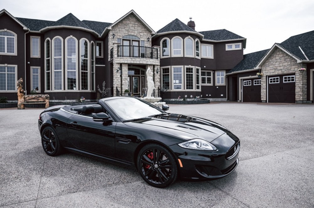 a sportscar in front of houses, blue color