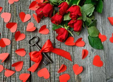 a key surrounded by red roses and hearts