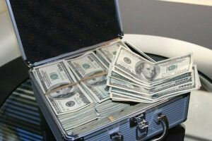 a suit case with many dollars